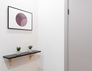 A framed picture of a circle hangs above a shelf with two plants.
